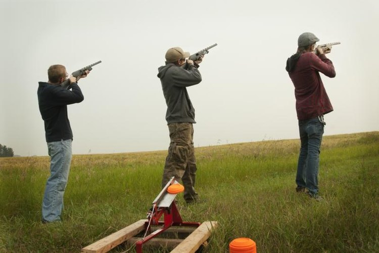 Three men practicing skeet shooting.