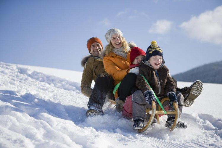 Family riding a toboggan down a snowy hill.