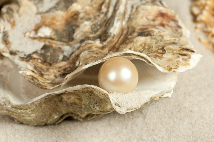 A large pearl in an oyster shell on sand.