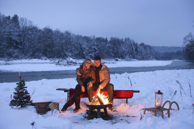Couple sitting in front of a campfire.