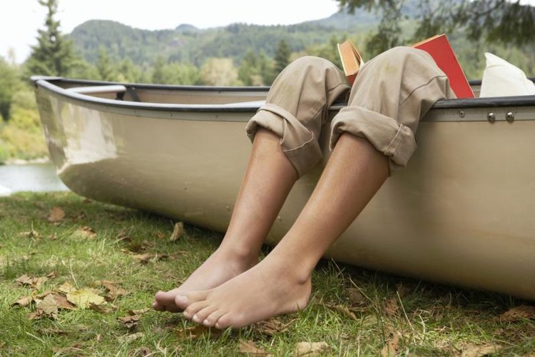 Feet hanging out of a canoe.
