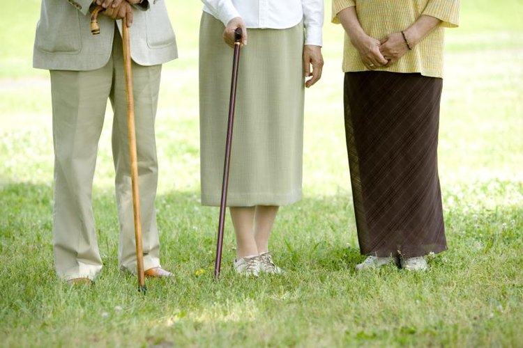 Close-up of elderly people holding walking sticks outside.