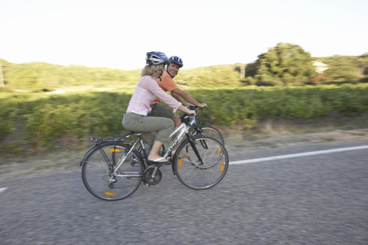 Two adults riding their bikes on the side of the road.