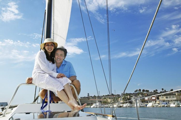 A smiling couple embracing on a sailboat.