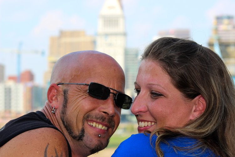 A smiling couple in front of the Cincinnati, Ohio skyline.