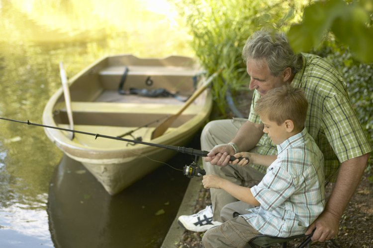 A father and his son fishing from the shore.