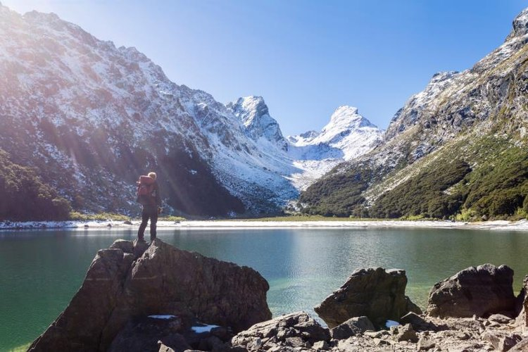 A hiker stands near Lake Mackenzie, Routeburn Track in Fiordland National Park, Southland, New Zealand.