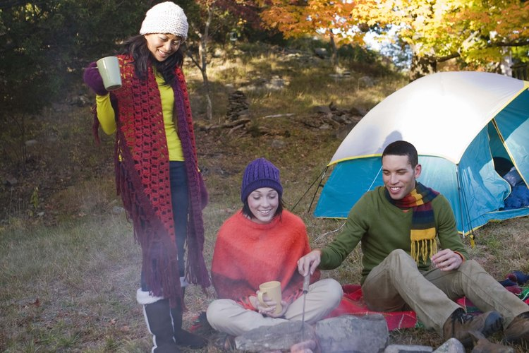 Young adults around campfire.