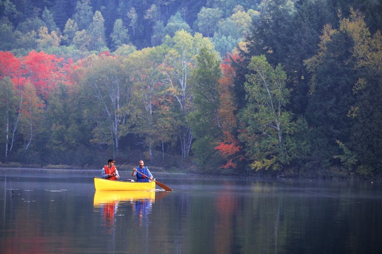People are fishing from a canoe.