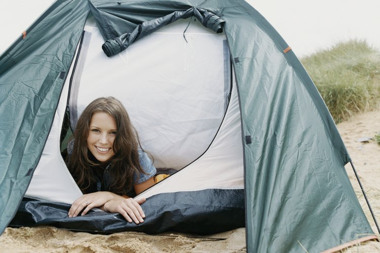Woman lying in a tent on a beach.