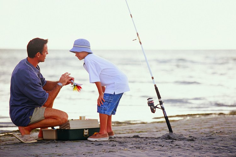 Father and son looking at bait to put on fishing pole.