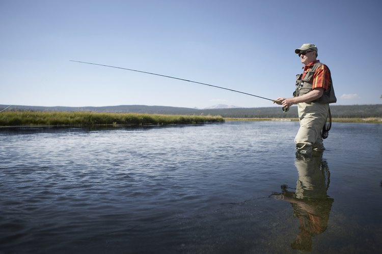 A man is fishing in a river.