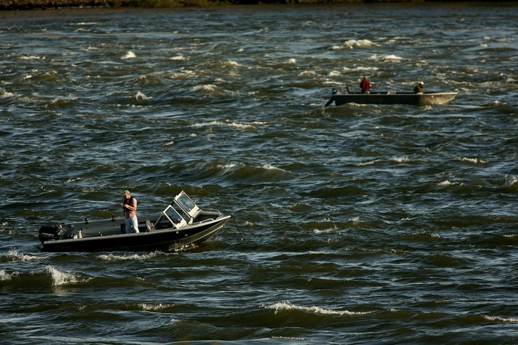 Men fish from boats on choppy Columbia River