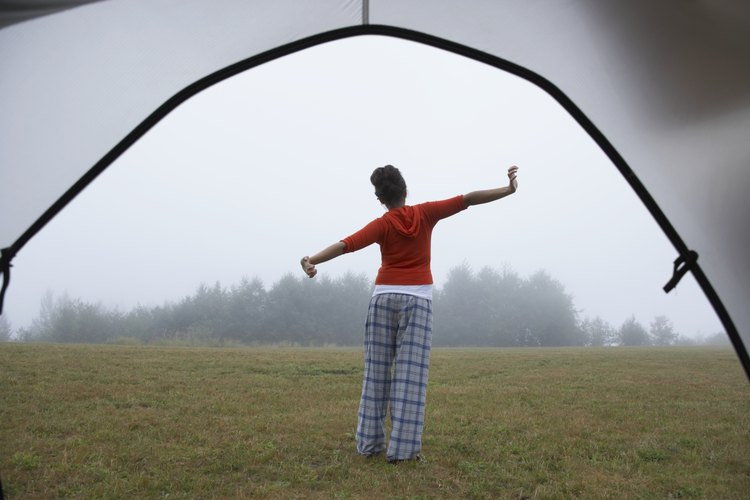 A woman stretching in the morning outside of a nylon tent.