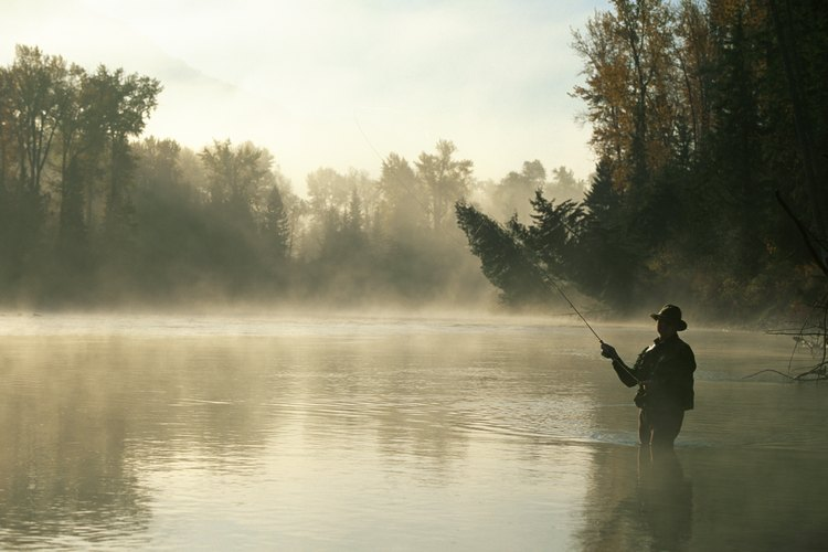 A man fly fishing in a river at sunrise.