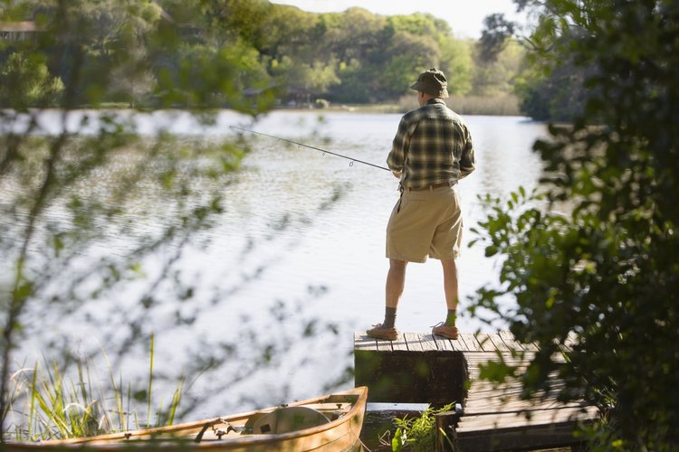 A man is standing on a dock holding a fishing pole.
