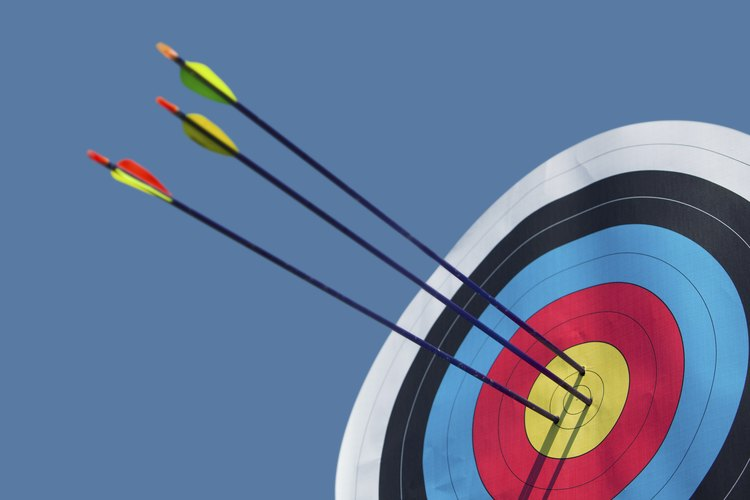 An archery target with three arrows in the bulls-eye.