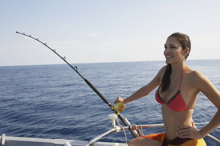 A young woman is saltwater fishing.