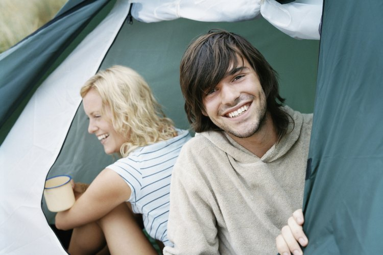Two friends smiling from the inside of a camping tent.
