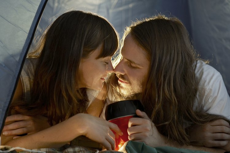 A young couple about to kiss inside of a tent.