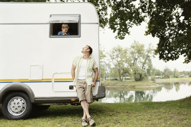 A man is leaning against a camper looking up at his son.