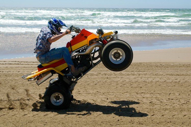 Someone is riding an ATV on the beach.