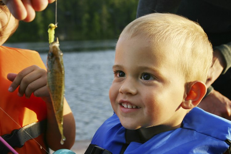 A young boy looks in amazement at a sunfish that his brother caught on a lake.