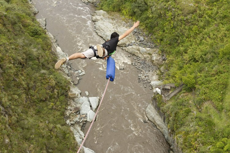 Man bungee jumping over river