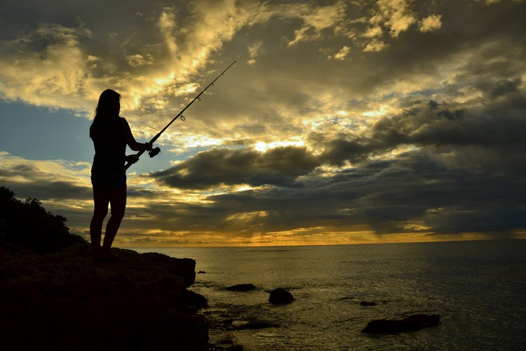 The silhouette of a woman fishing off a cliff in Oahu at sunset.