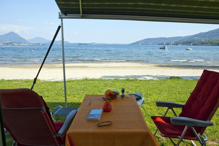 An outdoor table and camping chairs set up on a beach.