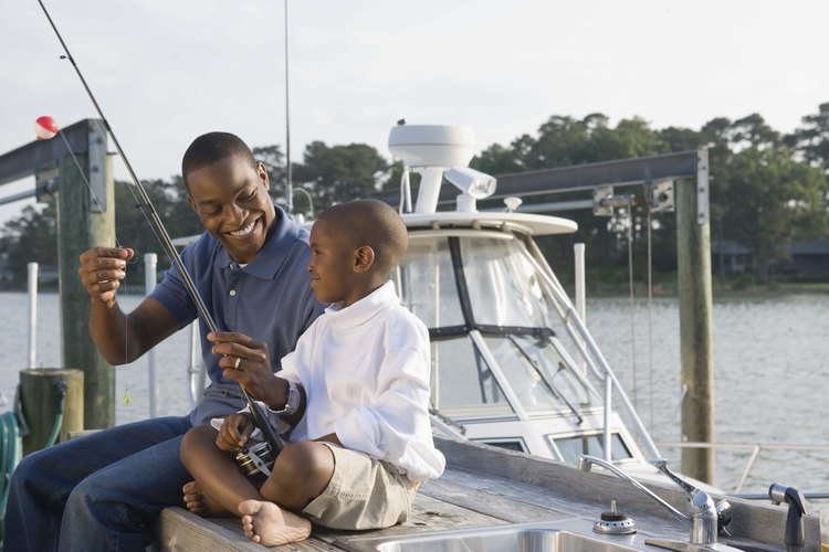 A father and son fishing off of a pier.