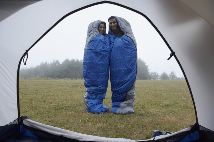 A couple standing in sleeping bags in front of a tent in the morning.