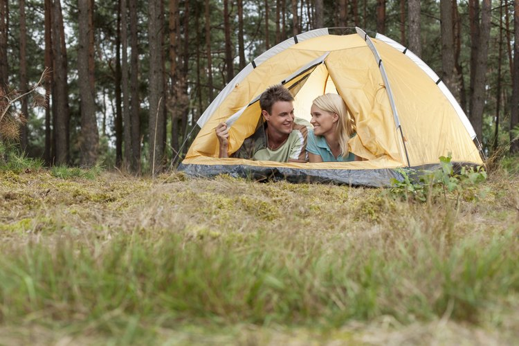 A young couple camping in a tent.