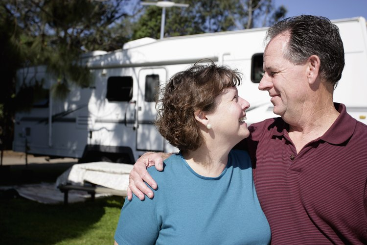 Couple embracing in front of an RV at a campground.