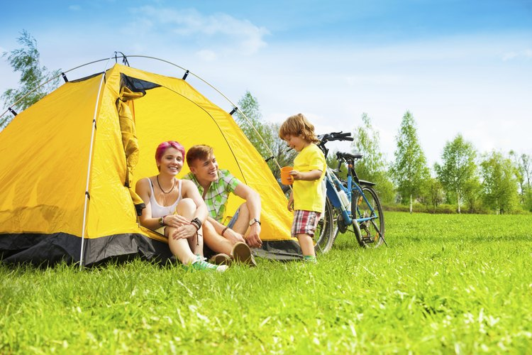 A young family camping in a tent.