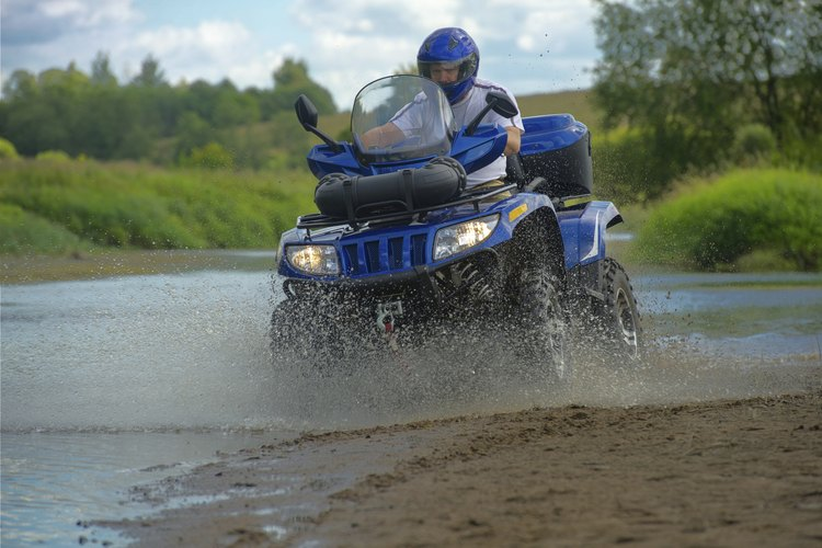 A man driving an ATV through water and mud in the woods.