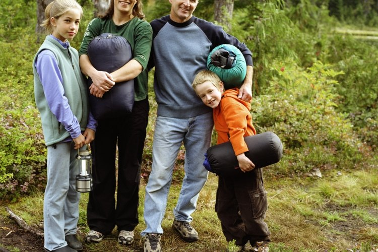 A family holding sleeping bags in Michaux State Forest, Pennsylvania.