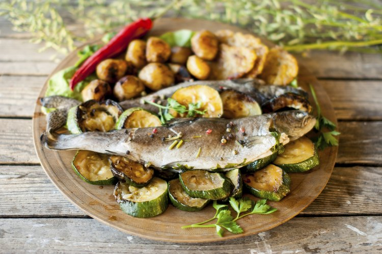Grilled trout with zucchini and baby potatoes on a wooden plate.