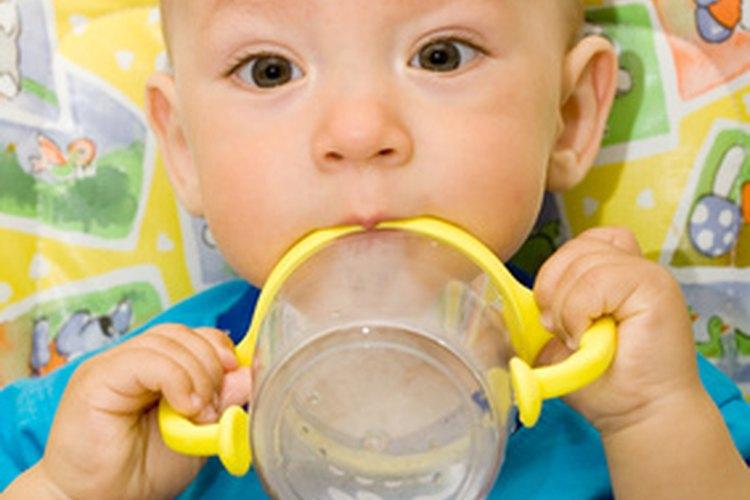 Usar un vasito entrenador con asas es una buena opción para tu bebé de seis meses.