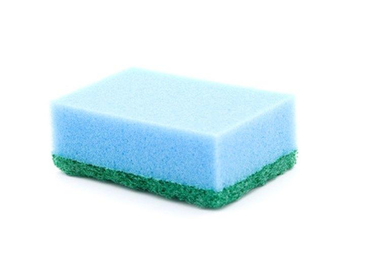 Moja una esponja limpia en agua clara.