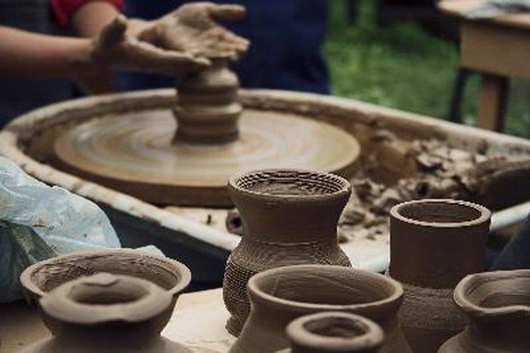 Coloca el trozo de arcilla en el centro de la rueda de cerámica y moldea el montículo a la forma deseada.