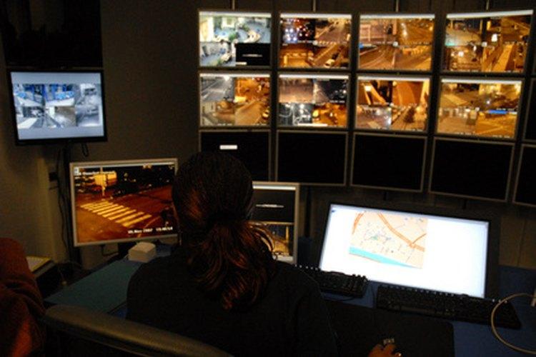 Algunos guardias de seguridad cuidan la seguridad del edificio mediante monitores de video.