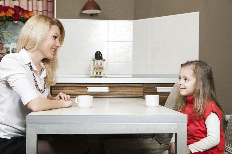 Madre joven y su hija hablando en una mesa.