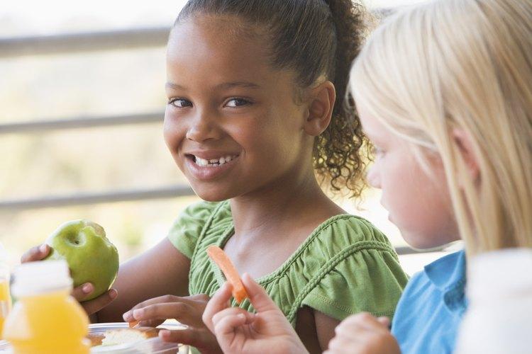 Niñas comiendo manzana y zanahoria en la escuela.