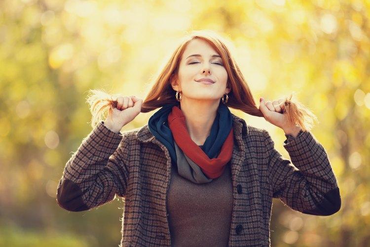 Una mujer de cabello colorado sonriendo al aire libre.