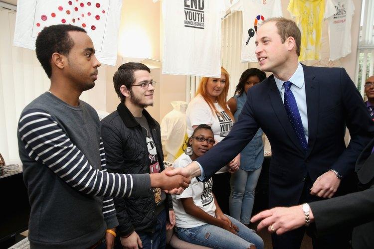 El príncipe William saluda a un trabajador de caridad.
