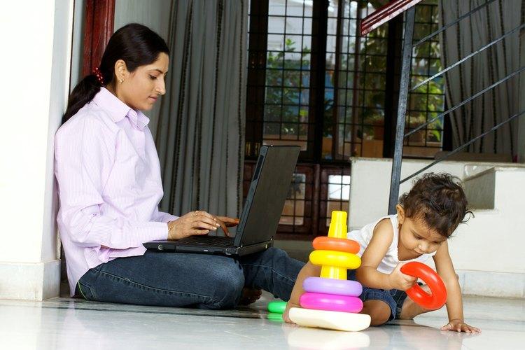 Mujer trabaja en la computadora portátil junto a un niño.