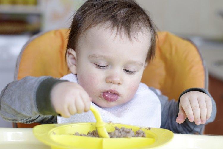 Bebé comiendo puré de alimentos en un plato pequeño.