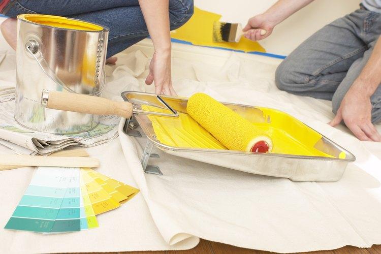 Mujer colocando la herramienta de pintura en la pintura.