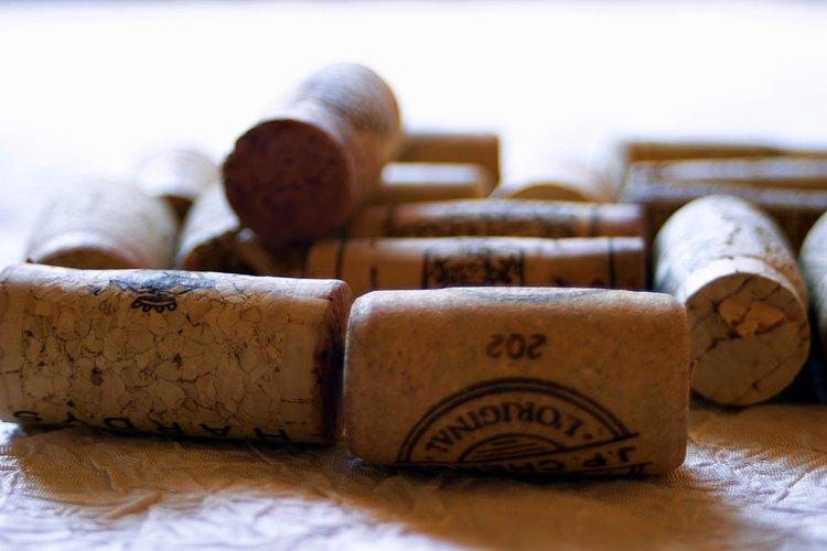 Corta corchos viejos de vino por la mitad para reciclarlos y hacer una alfombra para el baño.